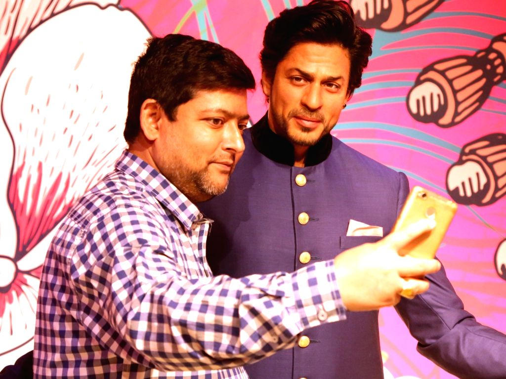 A fan poses for a selfie with the newly unveiled wax figure of actor Shah Rukh Khan, at Madame Tussauds in New Delhi on April 4, 2018. - Shah Rukh Khan