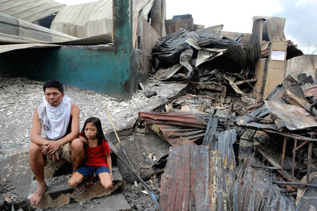 A father and his daughter sit in front of their burnt home after a fire at a residential area in Mandaluyong City, the Philippines, Nov. 14, 2016. 2 people ...