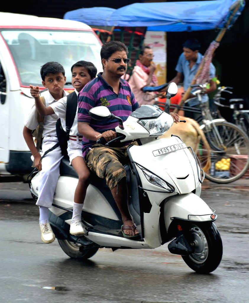 A father carrying their child to school on a scooter the 2nd day of curfew relaxations until 12pm as normalcy gradually returns in the tension-gripped Golaghat in Assam on Aug 23, 2014.