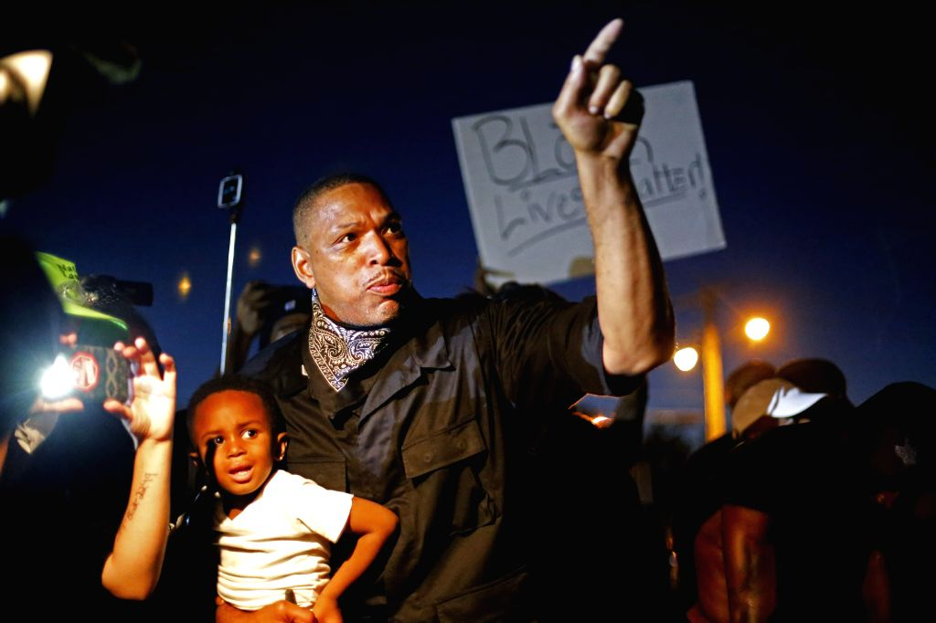 A father with his son in the arm reacts during a manifestation  in Ferguson, Missouri, the United States, on August 10, 2015. A state of emergency has been ...