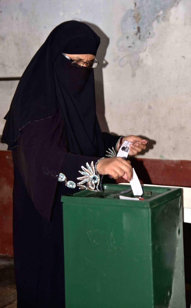 A female Muslim voter casts her ballot during voting for Greater Hyderabad Municipal Corporation (GHMC) elections, on Dec 1, 2020.