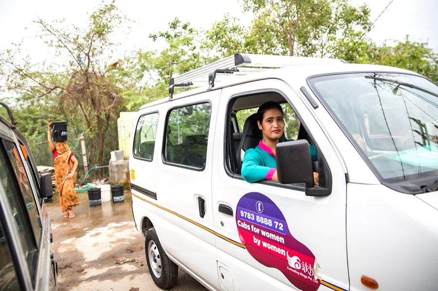A female Sakha chauffeur with her cab. (Photo Source: Azad Foundation/Sakha Consulting Wings)