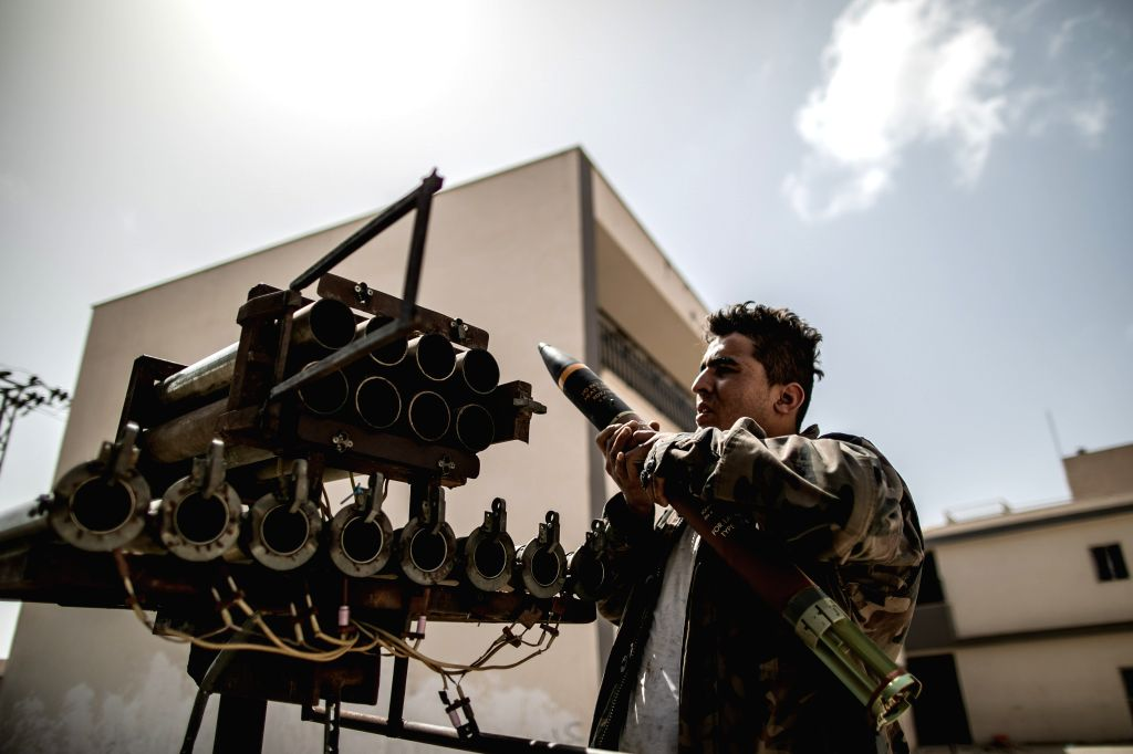 A fighter of the UN-backed Government of National Accord (GNA) inserts a missile into a rocket launcher at an abandoned school during clashes with East-based ...