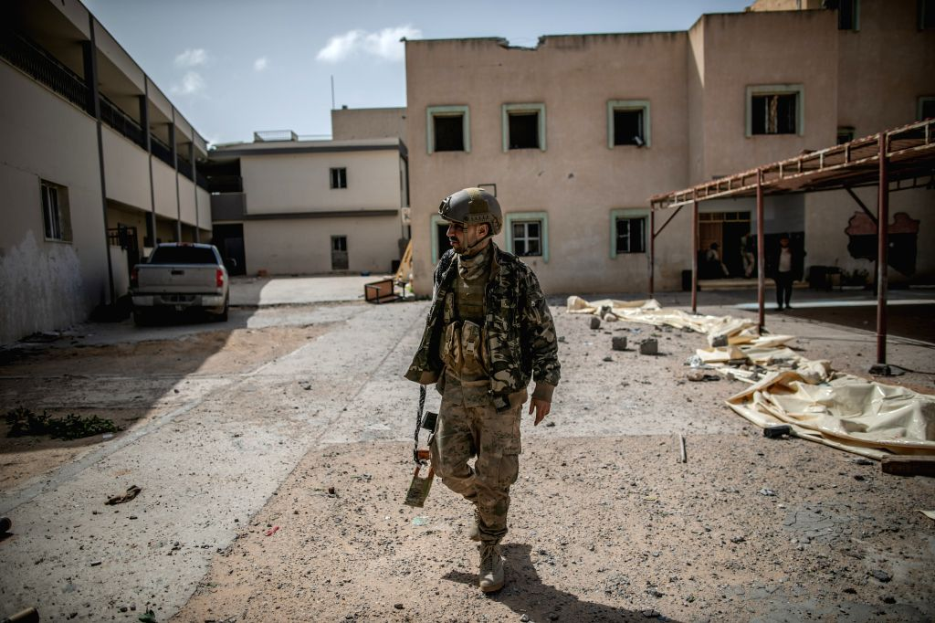 A fighter of the UN-backed Government of National Accord (GNA) is seen at an abandoned school during clashes with East-based Libyan National Army forces at Ain ...
