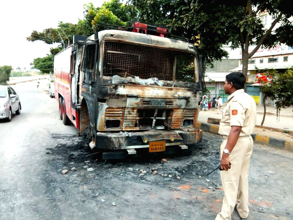A fire engine that was doused by protesters in Bengaluru on Sept 13, 2016. Uneasy calm prevailed in the city where one person was killed in police firing on Monday night and curfew is in ...