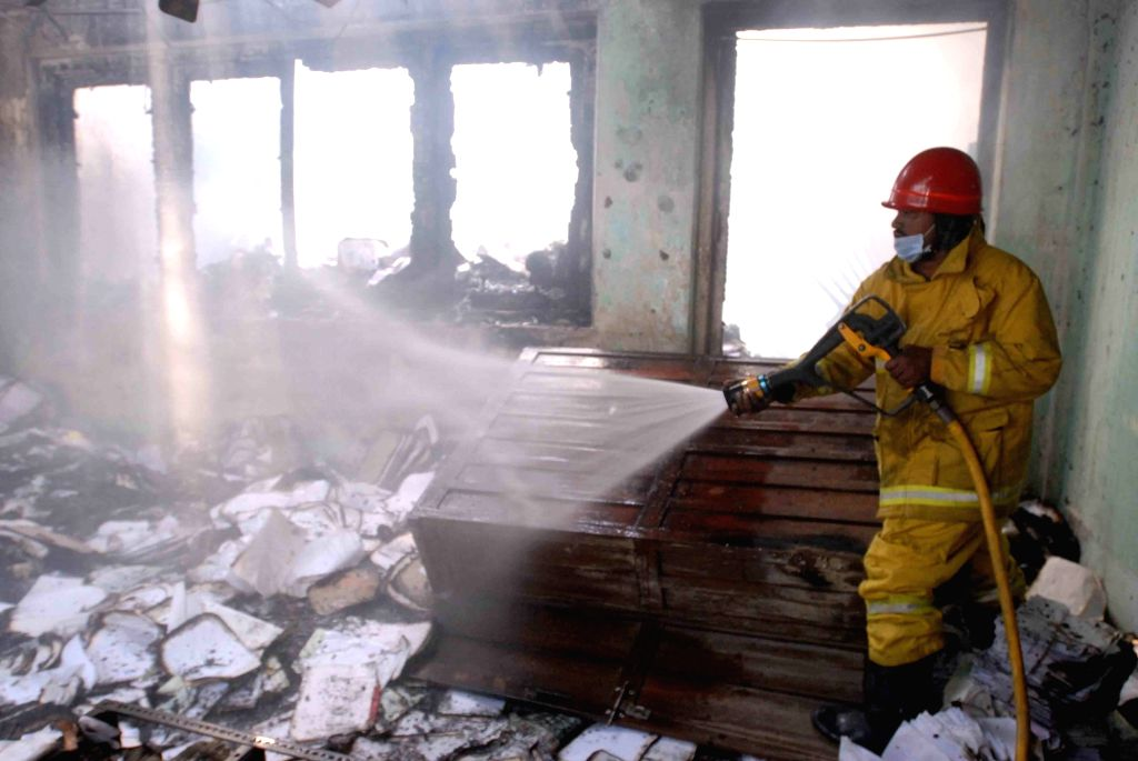A fire fighter douses fire after fire broke out at the record room of Road Transport Authority (RTA) office at Khairatabad in Hyderabad on Jan 24, 2018.