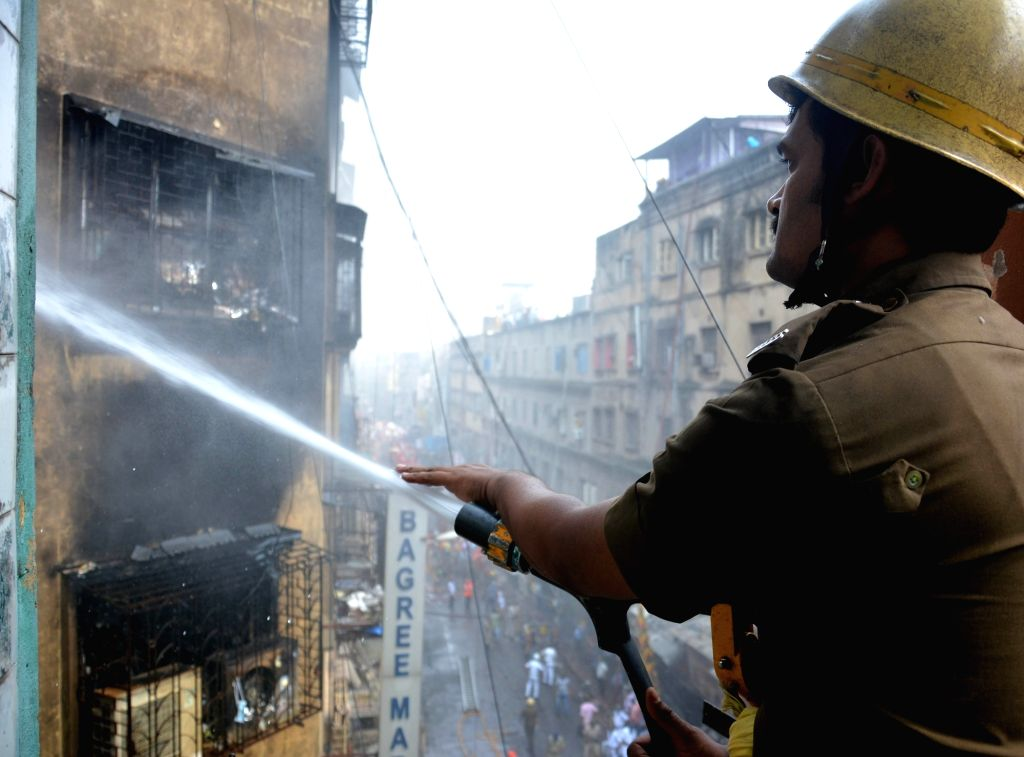 A firefighter douses fire that broke at Bagree market on Sunday; in Kolkata on Sept 18, 2018.