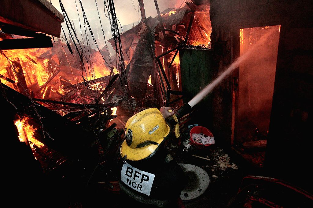 A firefighter tries to put out a fire at a slum area in Manila, the Philippines, Dec. 4, 2015. More than 500 shanties were razed in the fire, leaving 1,000 families ...