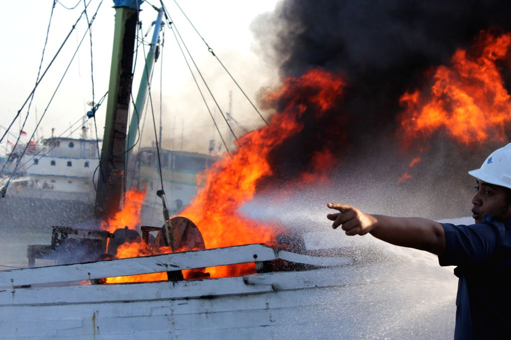 A fireman tries to extinguish the fire on a ship carrying 800 tons of fertilizer in Gresik Port, East Java, Indonesia, Aug. 25, 2015. The fire was caused by ...