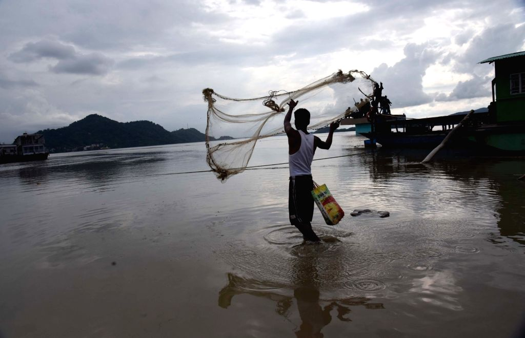 A fisherman casts his net in Brahmaputra river in Guwahati, on July 3, 2017.