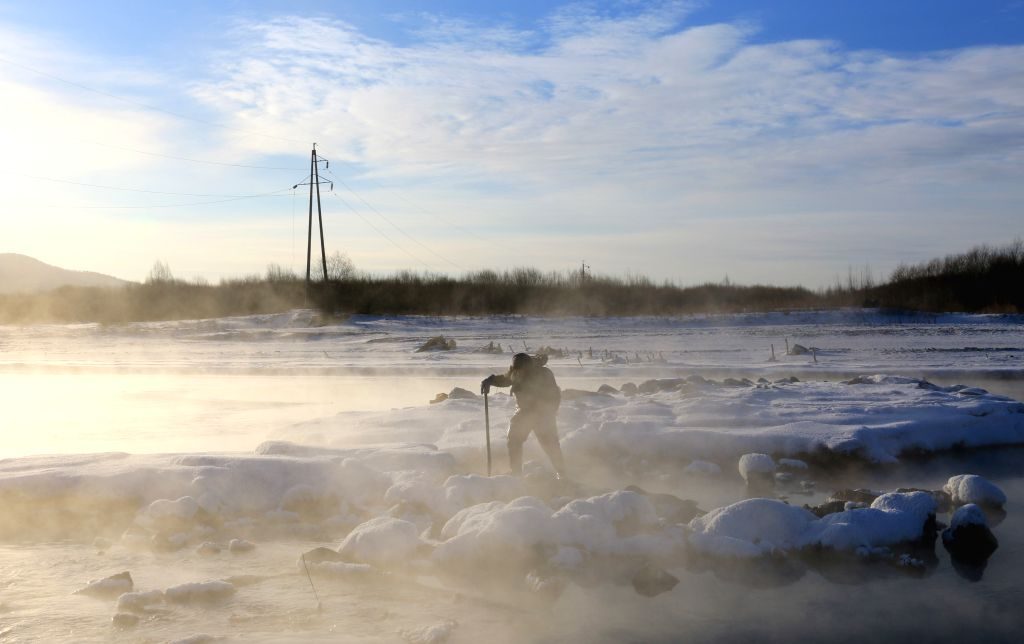 A fisherman walks by the mist-enveloped Ganhe River in Greater Hinggan Mountains region, northeast China's Heilongjiang Province, Jan. 10, 2016. ...
