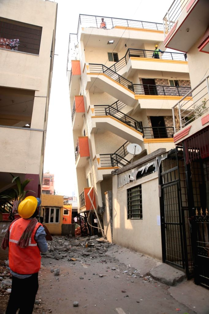 A five-storeyed building that got tilted due to the construction of another building nearby, posing a threat to the residents of the locality, being demolished, at Kempapura, ...