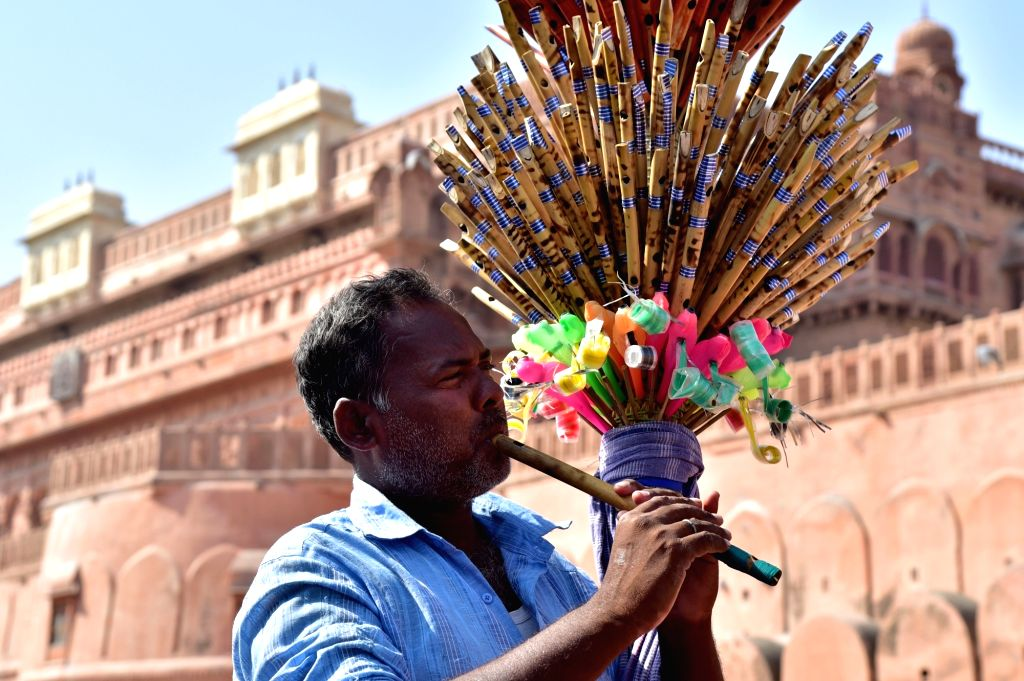 A flute seller plays flute as he walks down the Bikaner streets playing flute on Oct 12, 2017.