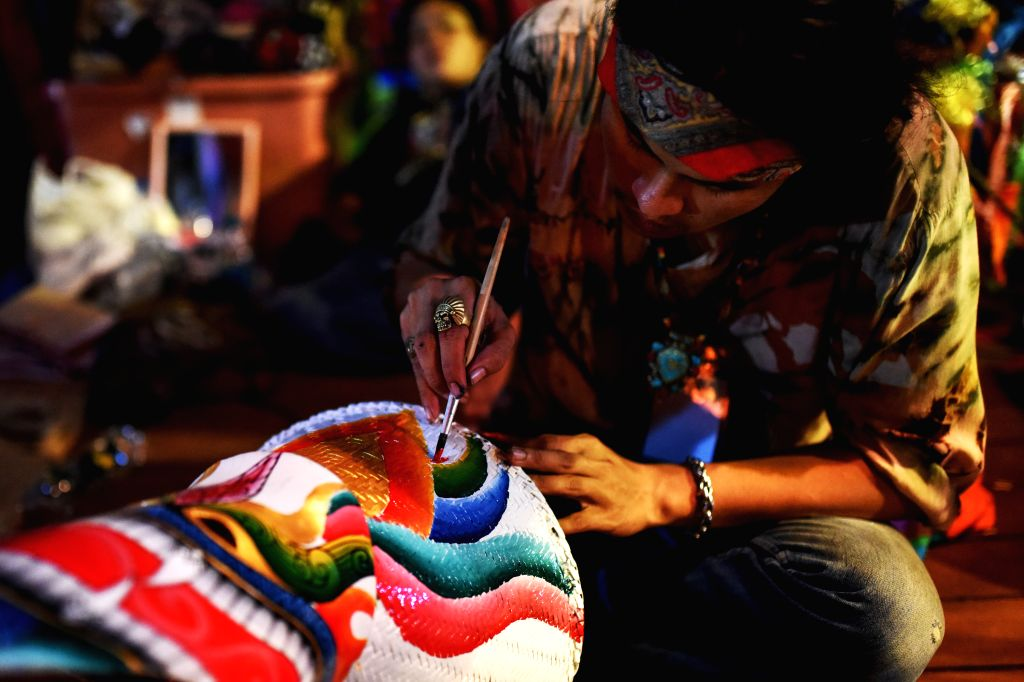 A folk artist draws color patterns on a handcrafted mask during the 36th Thailand Tourism Festival at the Lumphini Park in Bangkok, Thailand, Jan. 13, 2016. ...