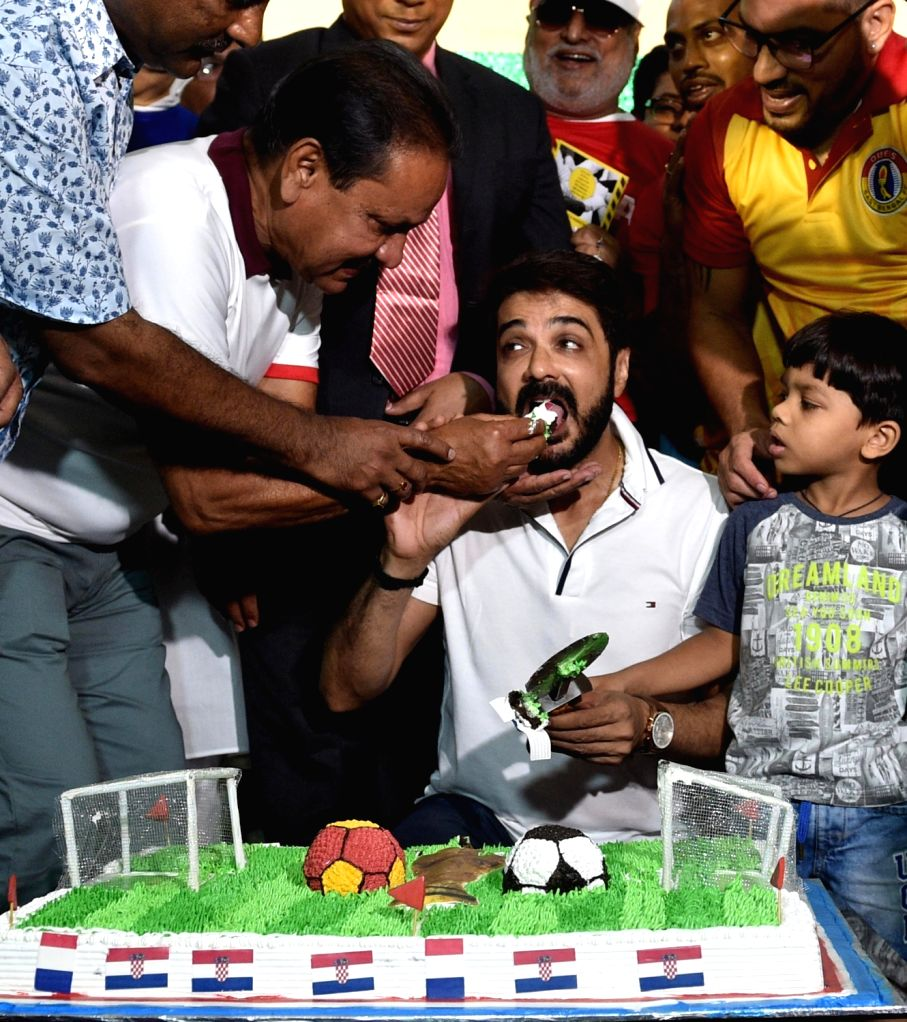 A football enthusiast fetches a piece of cake to actor Prosenjit Chatterjee as they cheer ahead of FIFA World Cup 2018 final match between France and Croatia, in Kolkata on July 15, 2018. - Prosenjit Chatterjee