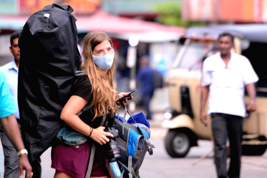 A foreign tourist waits for a train at the railway station in Colombo, Sri Lanka, on March 18, 2020. Sri Lanka has so far confirmed 43 positive COVID-19 patients ...