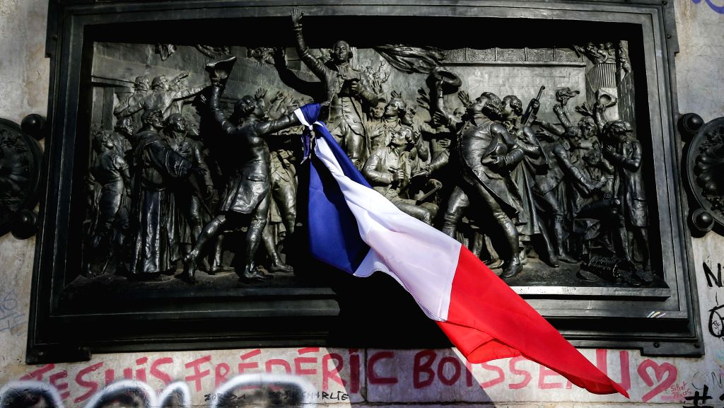 A French national flag is seen on the monument at the Place de la Republique square to mourn for the victims of the terrorist attacks in Paris, capital of France, ...