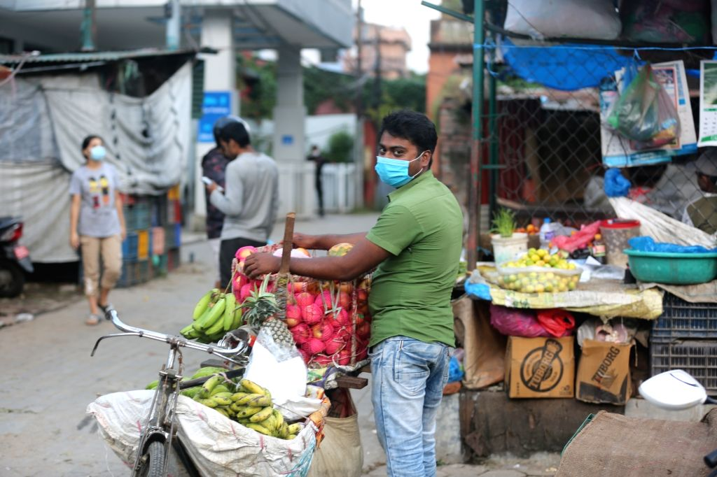 A fruit vendor wearing a face mask is seen on a street in Kathmandu, Nepal, Sept. 13, 2020. Despite rising cases, the Nepali local administrations in the ...