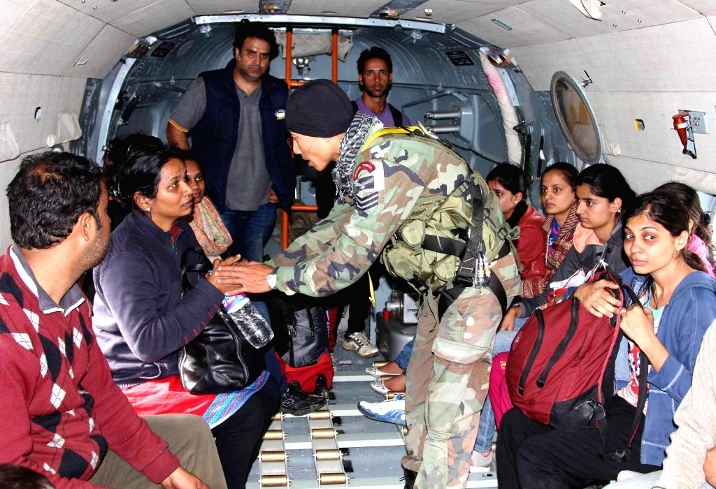 A Garud commando consoles one of the rescued persons onboard an aircraft in Srinagar on September 09, 2014.