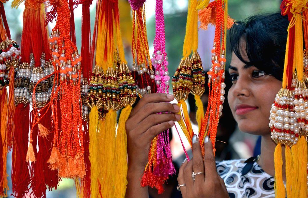A girl buys rakhi ahead of Raksha Bandhan in Agra, on Aug 16, 2016.