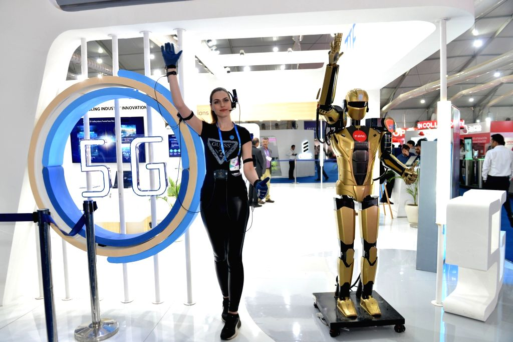 A girl demonstrates the use of 5G technology with the help of a robot at the India Mobile Congress 2019 in New Delhi on Oct 16, 2019.