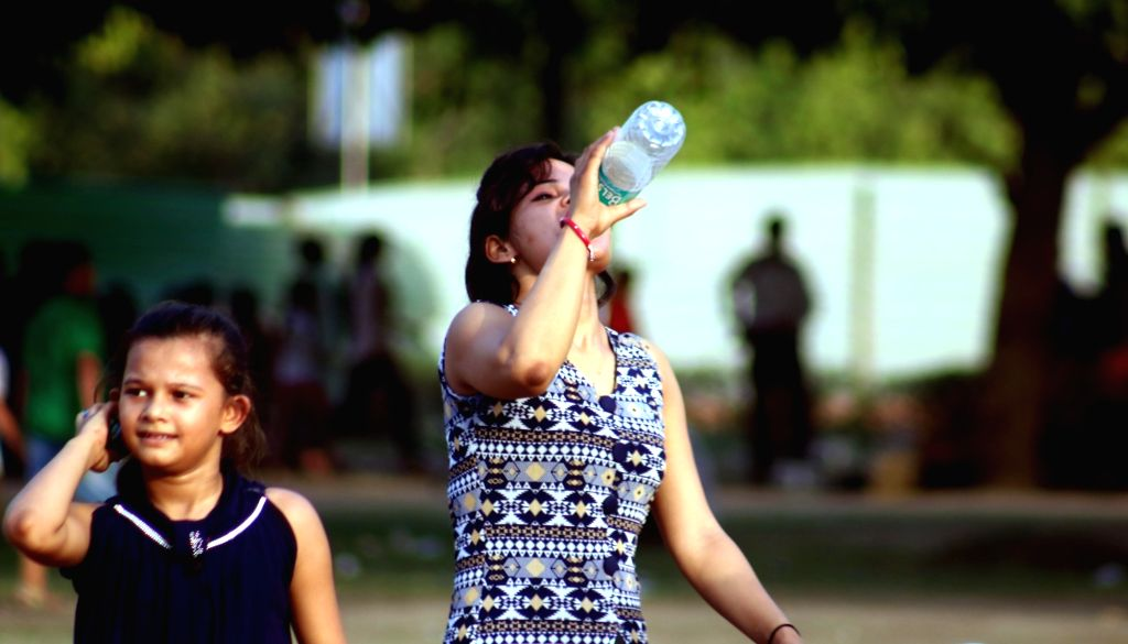A girl drinks water to beat the heat on a hot day in New Delhi on June 3, 2016.