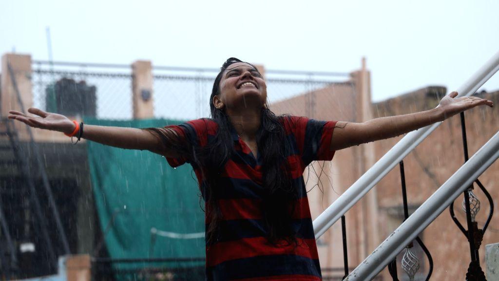 A girl enjoys herself in the rain in New Delhi on June 24, 2020.