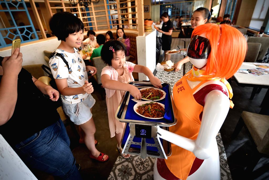 A girl takes dishes delivered by the robot waiter in Haikou, capital of south China's Hainan Province, Aug. 3, 2015. A robot waiter was introduced to a restaurant in ...