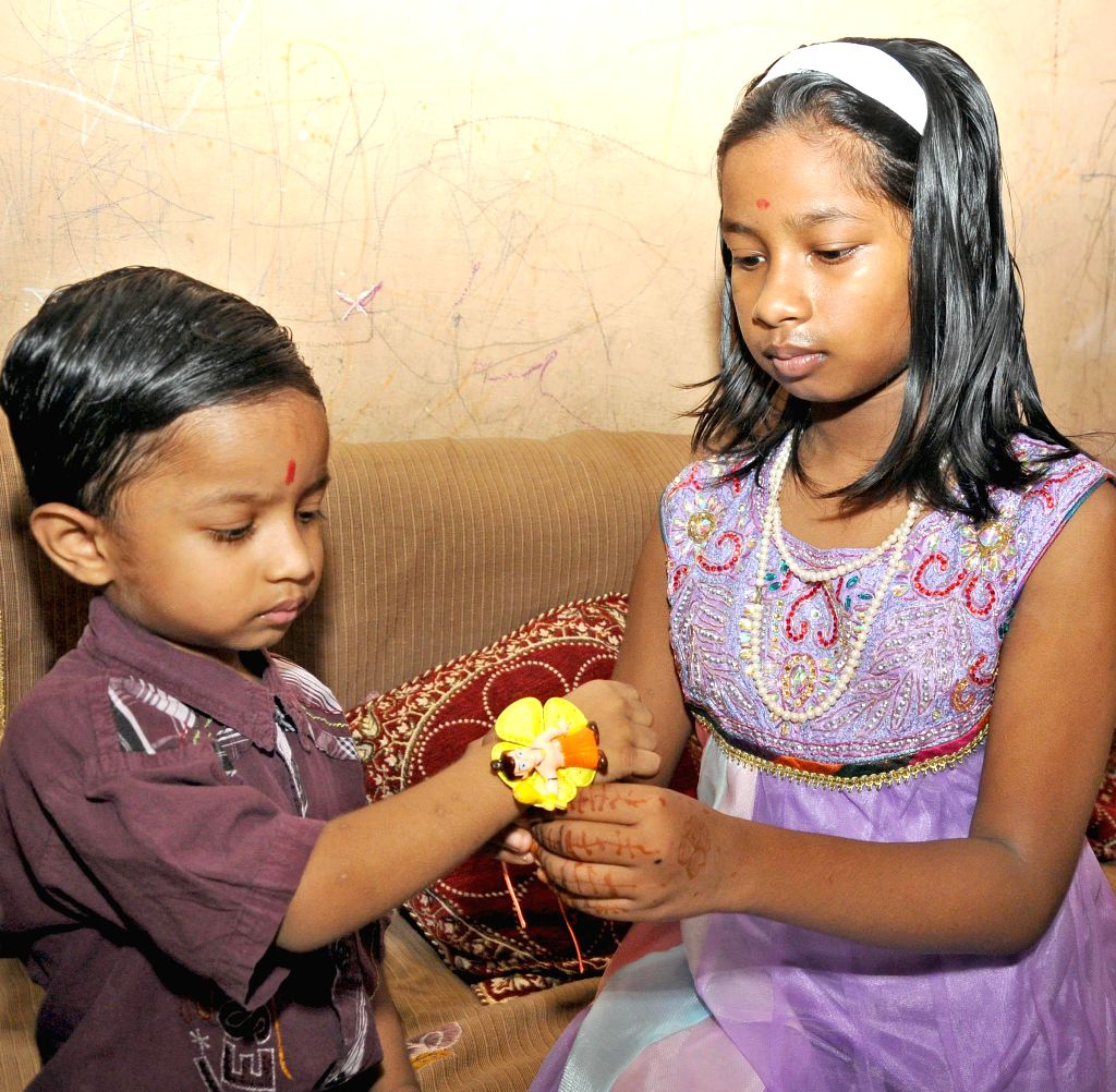 A girl ties a `rakhi` on the wrist of her brother on 'Raksha Bandhan' in New Delhi on Aug 10, 2014.