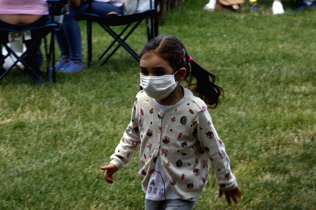 A girl wearing a mask plays at a park in Ankara, Turkey, on June 25, 2020. Turkey reported 1,458 new coronavirus cases and 21 fatalities in the past 24 hours, taking ... - Fahrettin Koca
