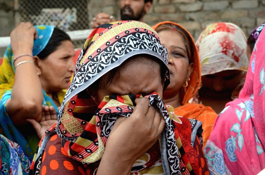 A grief-stuck relative of the person who was killed in a fire that broke out at a fireworks manufacturing unit, in Amritsar on May 30, 2018.