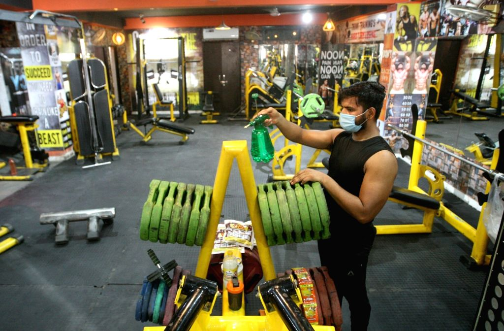 A gym staff sanitises gym equipments after the Delhi Government as the Yoga institutes and gymnasiums are slated to open from tomorrow as a part of the third phase of easing of COVID-19 ...