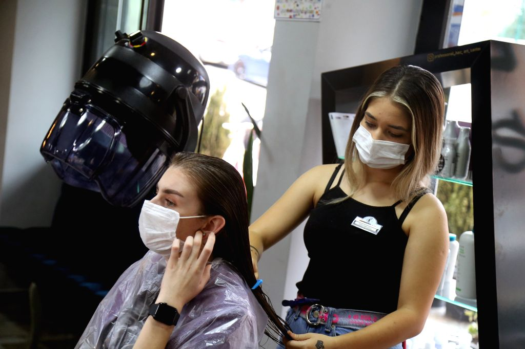 A hairdresser wearing a face mask serves a customer at a hairdressing salon in Ankara, Turkey, on Sept. 12, 2020. Turkey confirmed 1,509 new COVID-19 cases on ...