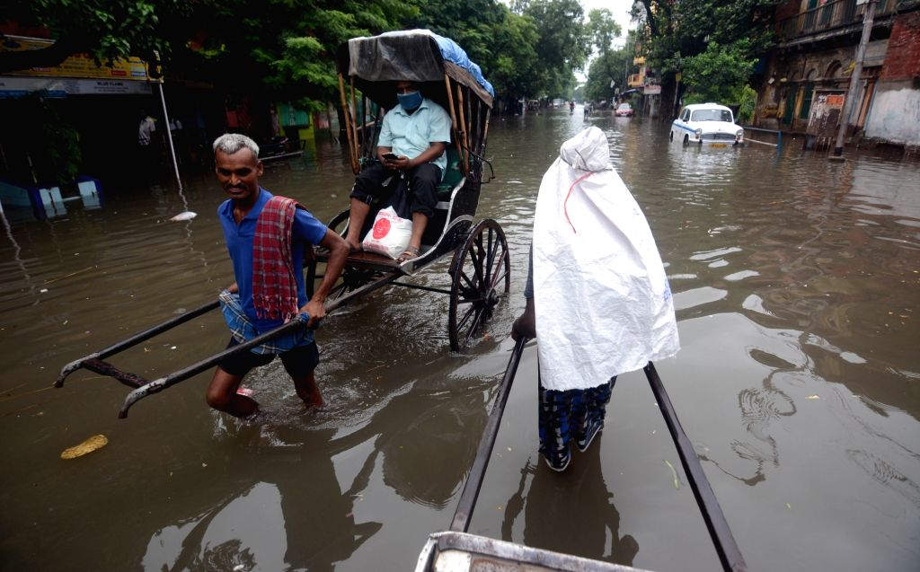 A hand rickshaw puller wades through a water-logged street during heavy rainfall in Kolkata on Thursday 17 June 2021.