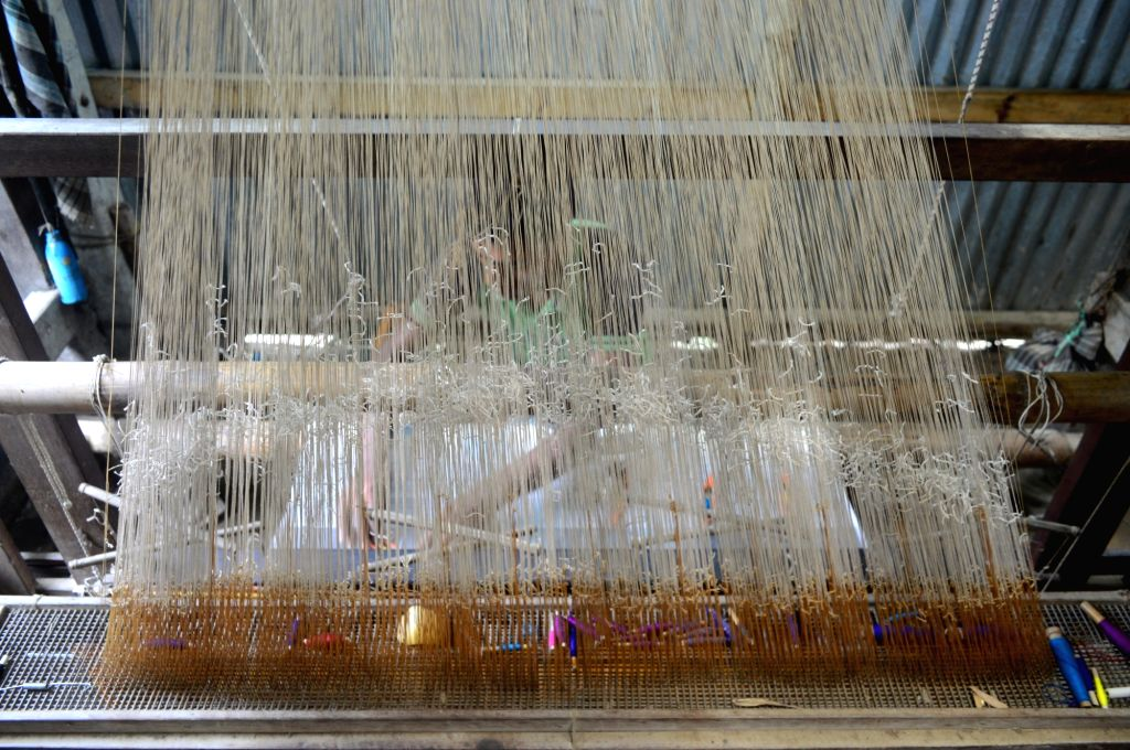 A handloom artist weaves silk on his pit loom in Agomoni in Dhubri district of Assam.