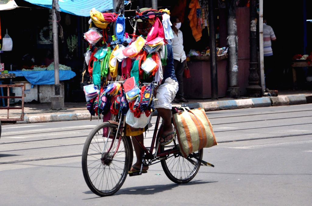 A hawker sells colorful masks on a cycle as he paddles past a deserted Kolkata street amid COVID-19 pandemic on June 25, 2020.