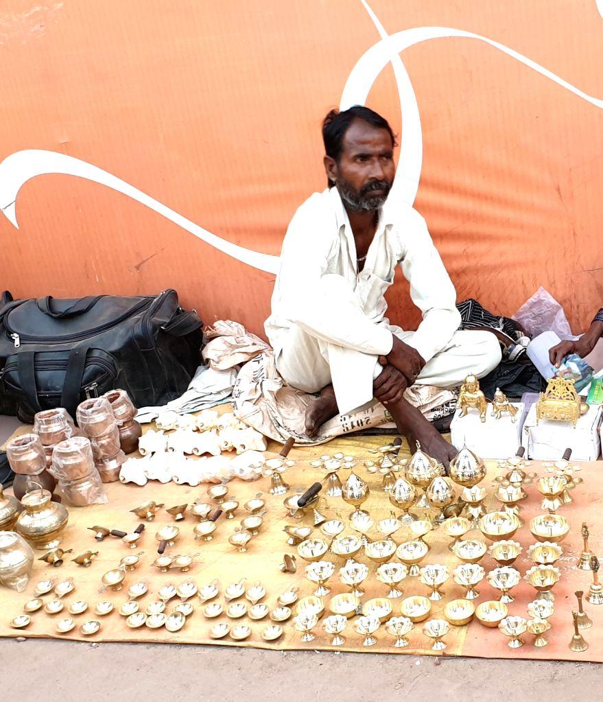 A hawker sells metal lamps during Kumbh at Sangam in Prayagraj.