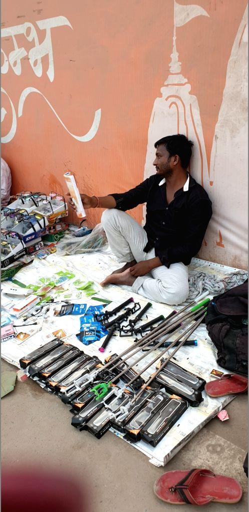 A hawker sells selfie sticks during Kumbh at Sangam in Prayagraj.