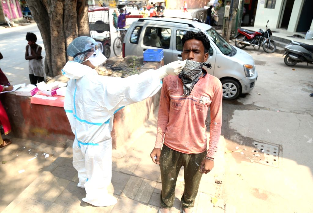 A health worker collectes swab samples from people for COVID-19 rapid antigen tests, in New Delhi on Sep 24, 2020.
