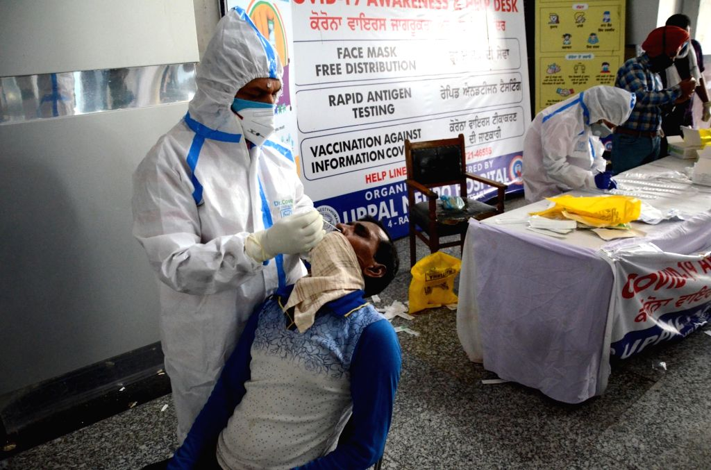 A health worker collects a nasal swab sample from a passenger to test for the Covid-19 coronavirus at a railway station in Amritsar on Wednesday, 12 May, 2021