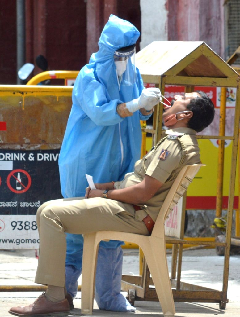 A health worker collects swab samples for COVID-19 testing from a police personnel at Kalasipalya police station in Bengaluru on June 23, 2020.