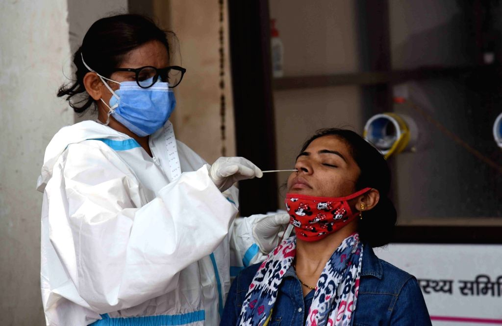 A health worker collects swab samples from a woman for Covid-19 test, amid a countrywide spike in coronavirus cases, at a government dispensary, in Patna On Friday, 16th April,2021.