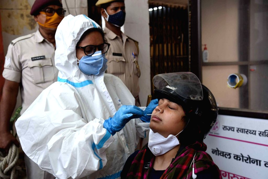 A Health worker collects swab samples from a people for COVID-19 test, amid rise in Covid-19 cases across the country, at government health center in Patna, Sunday, April 18, 2021.