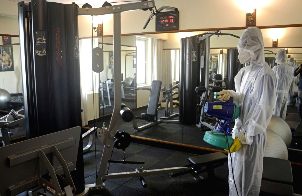 A health worker sanitises a hotel gym in Kolkata amid COVID-19 pandemic, on Aug 4, 2020.