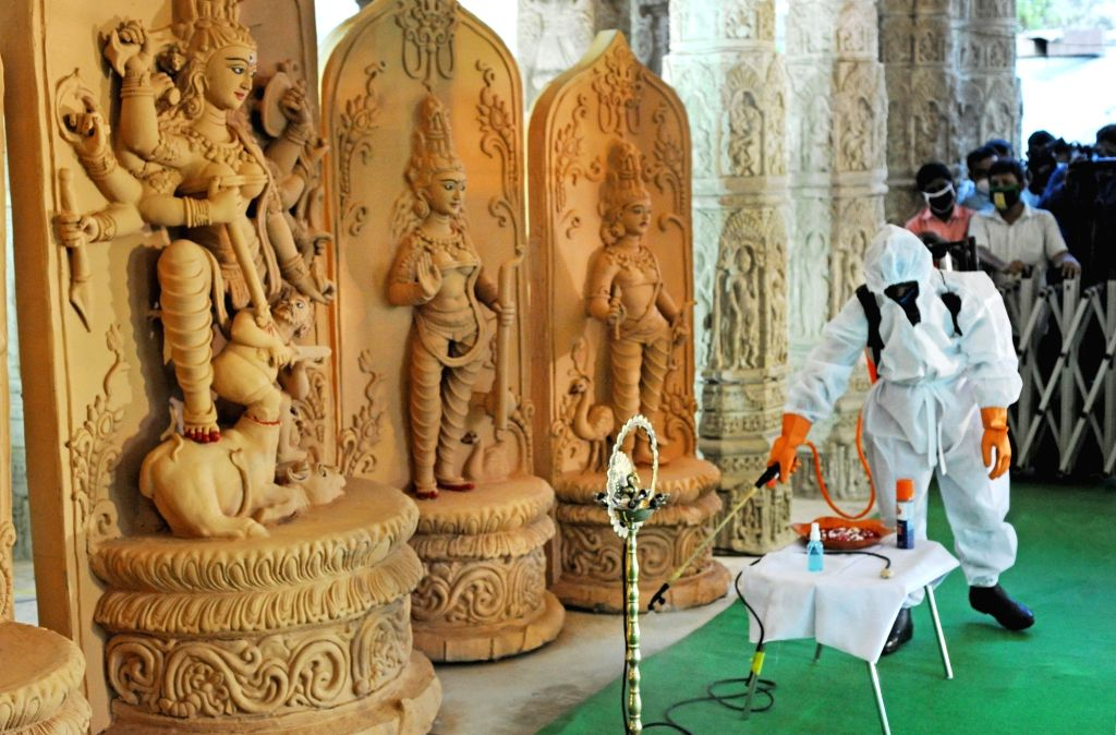 A health worker sanitises the community Puja pandal ahead of West Bengal Chief Minister Mamata Banerjee's arrival to inaugurate Ahiritola Durgotsav on the eve of Durga Puja celebrations, in ... - Mamata Banerjee
