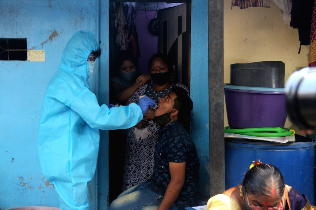 A health worker swab test of a resident for COVID-19 following rise in coronavirus cases at Dharavi in Mumbai, Maharashtra on Tuesday 23rd February, 2021.  .