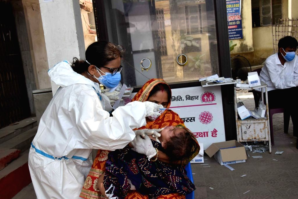 A health worker takes a nasal sample from a people for COVID-19 testing, in Patna On Saturday, 08 May, 2021.