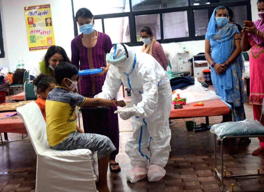 A health worker ties a rakhi to a COVID-19 patient at CWG Village Covid Care Center in New Delhi on Aug 3, 2020.