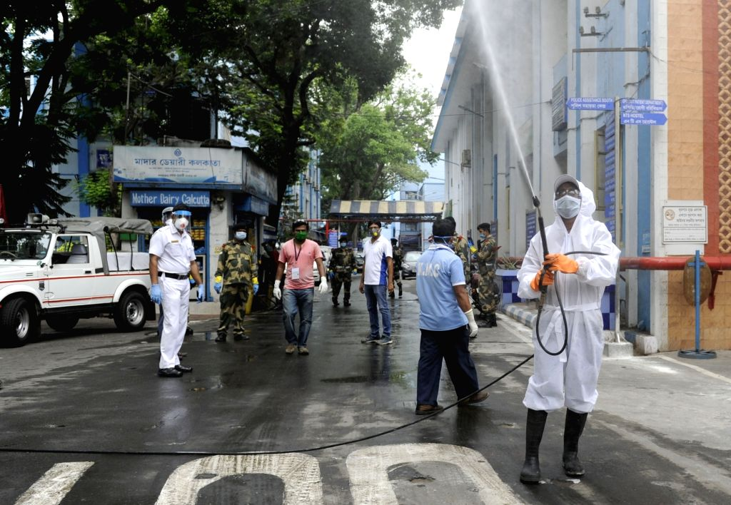 A health worker wearing a Personal Protective Equipment (PPE) suit sprays disinfectants at Kolkata's M R Bangur Hospital where a central vigilance team visited during the extended nationwide ...