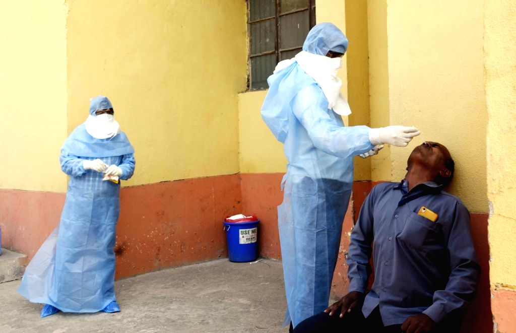 A health worker wearing Personal Protective Equipment (PPE) suit collects nasal swab from a person at a Patna COVID-19 testing center during the extended nationwide lockdown imposed to ...